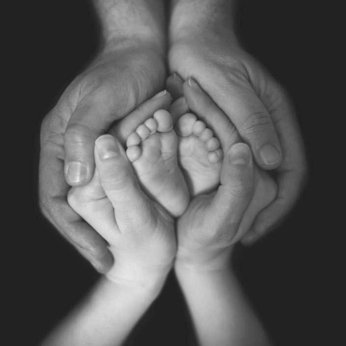 Fotografia di genitori che tengono nelle mani i piedini del bambino a formare un fiore