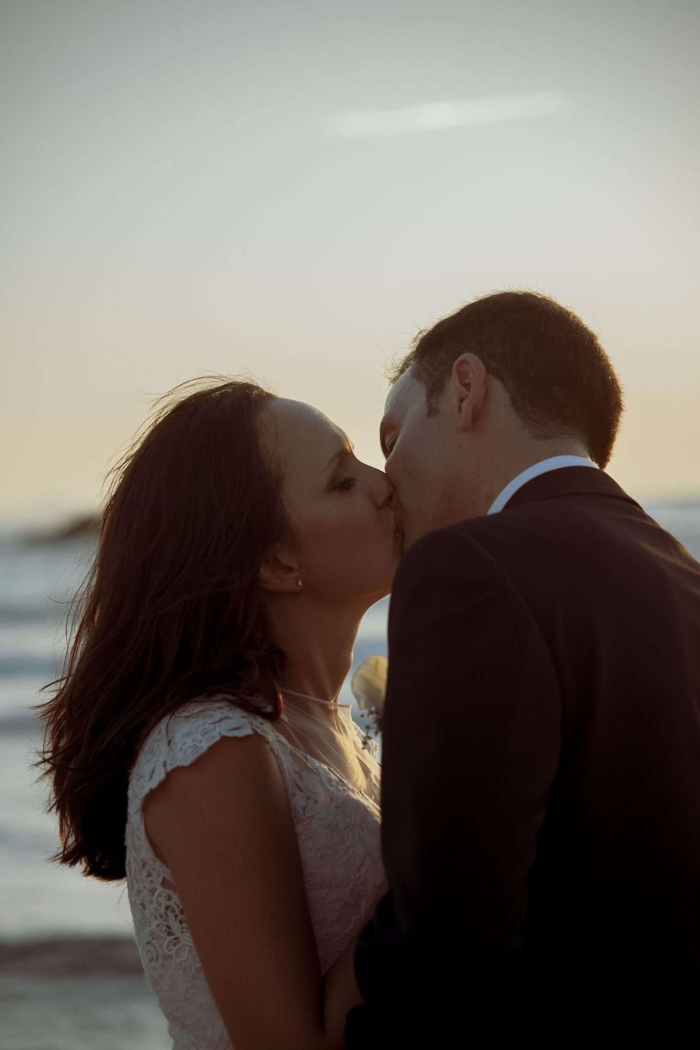 Sposi che si baciano al tramonto in spiaggia - Wedding Reportage