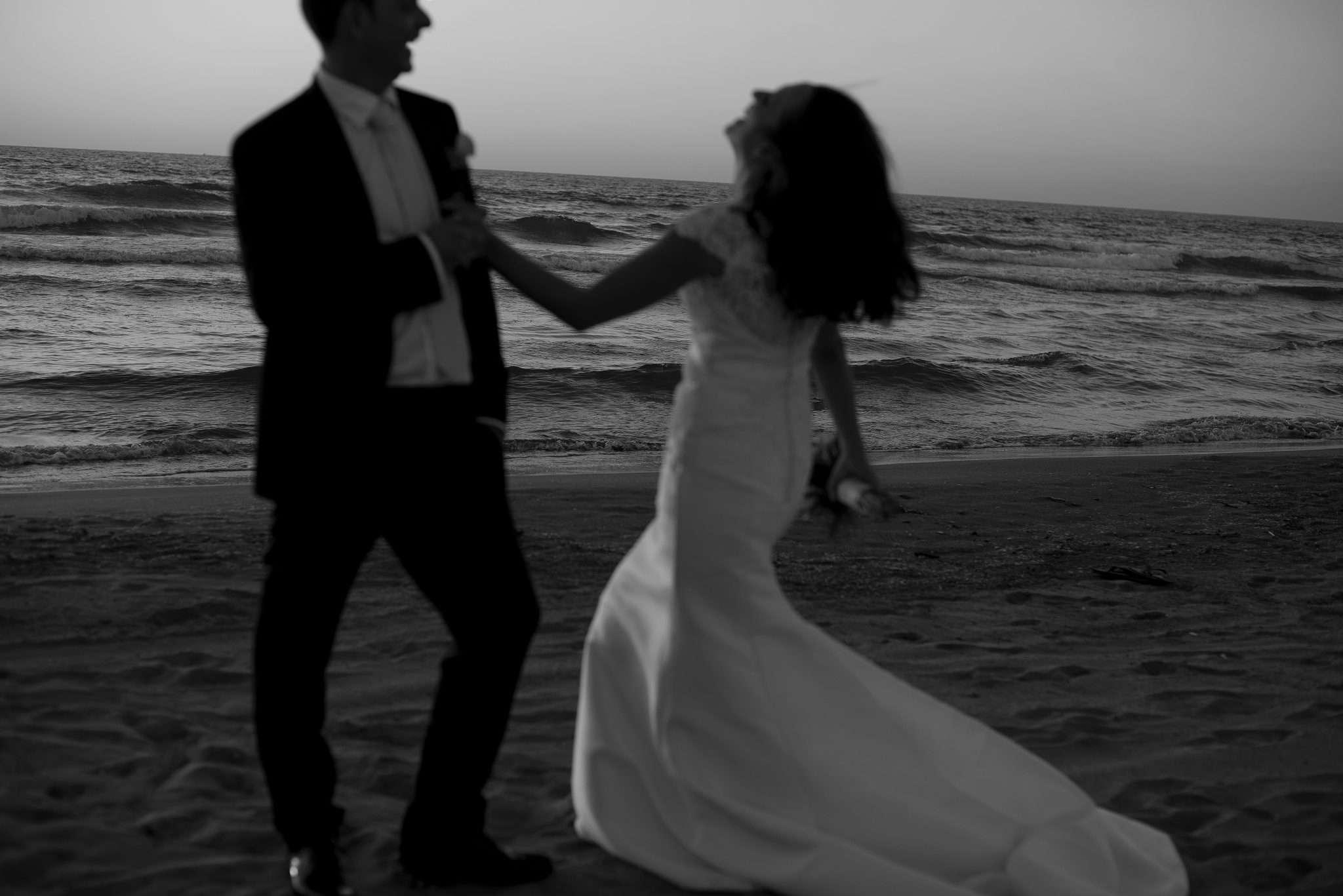 Giovani sposi sorridenti che ballano in spiaggia