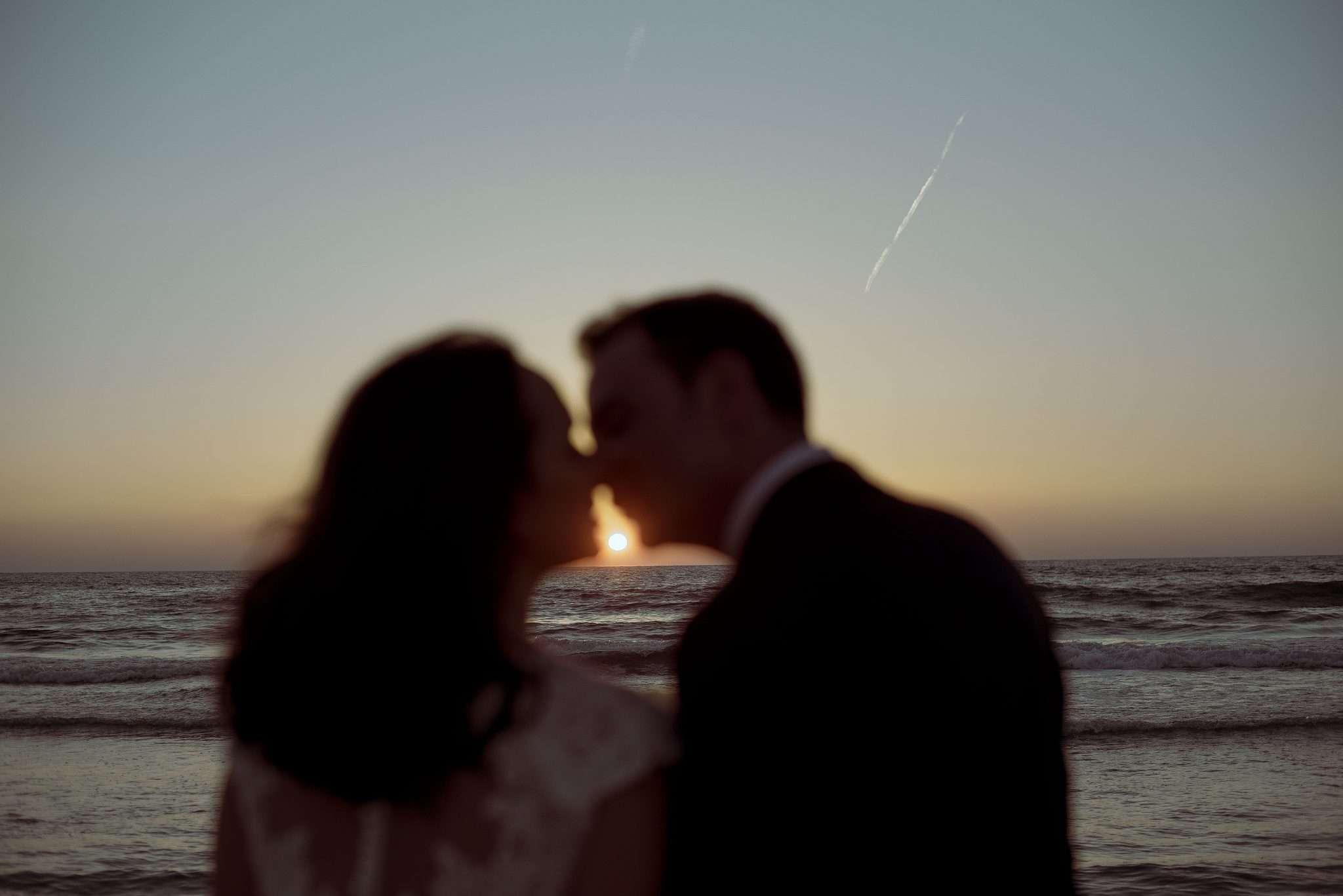 Sposi che si baciano al tramonto sul litorale di bacoli