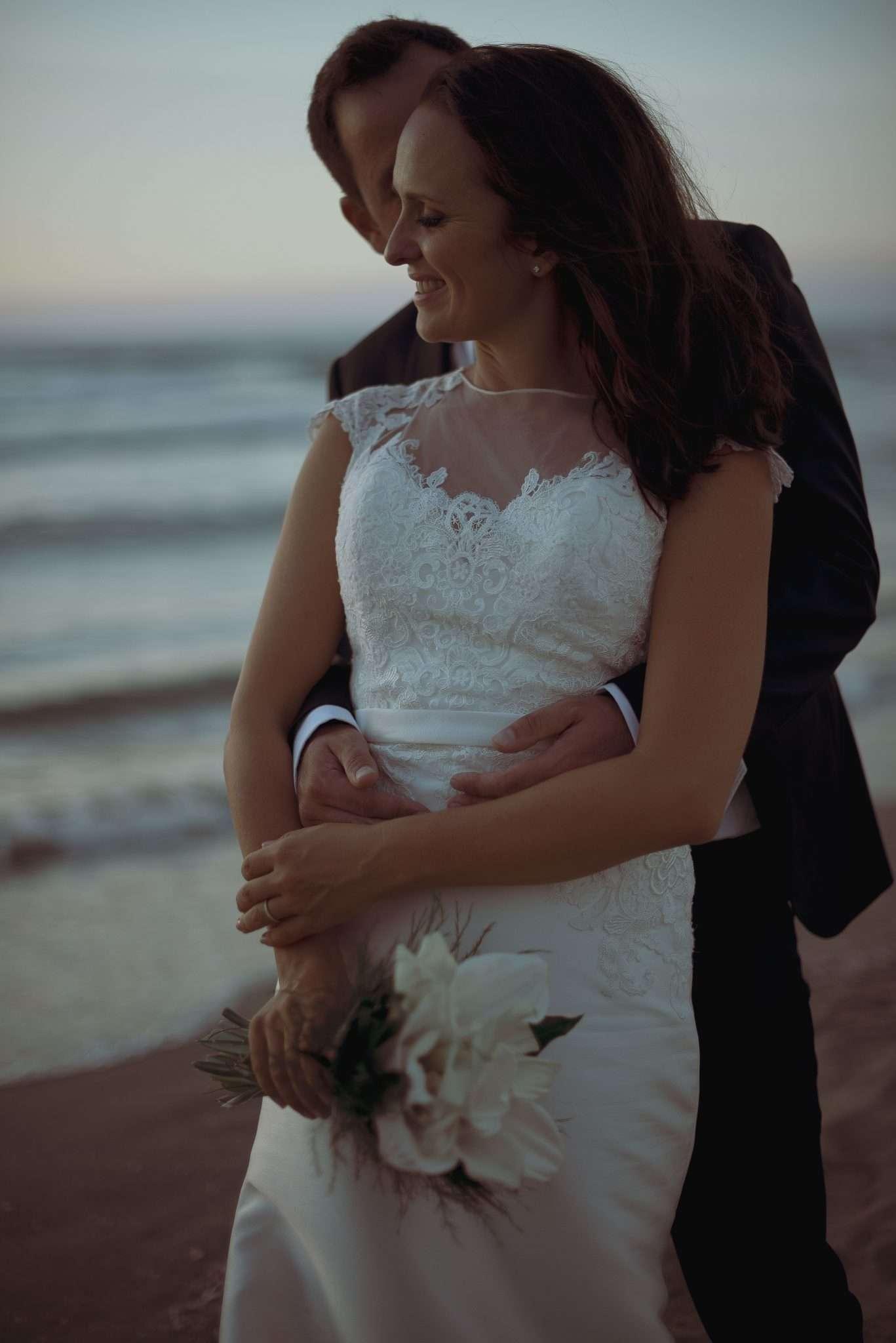 Sposo che abbraccia sposa al tramonto sulla spiaggia di Bacoli