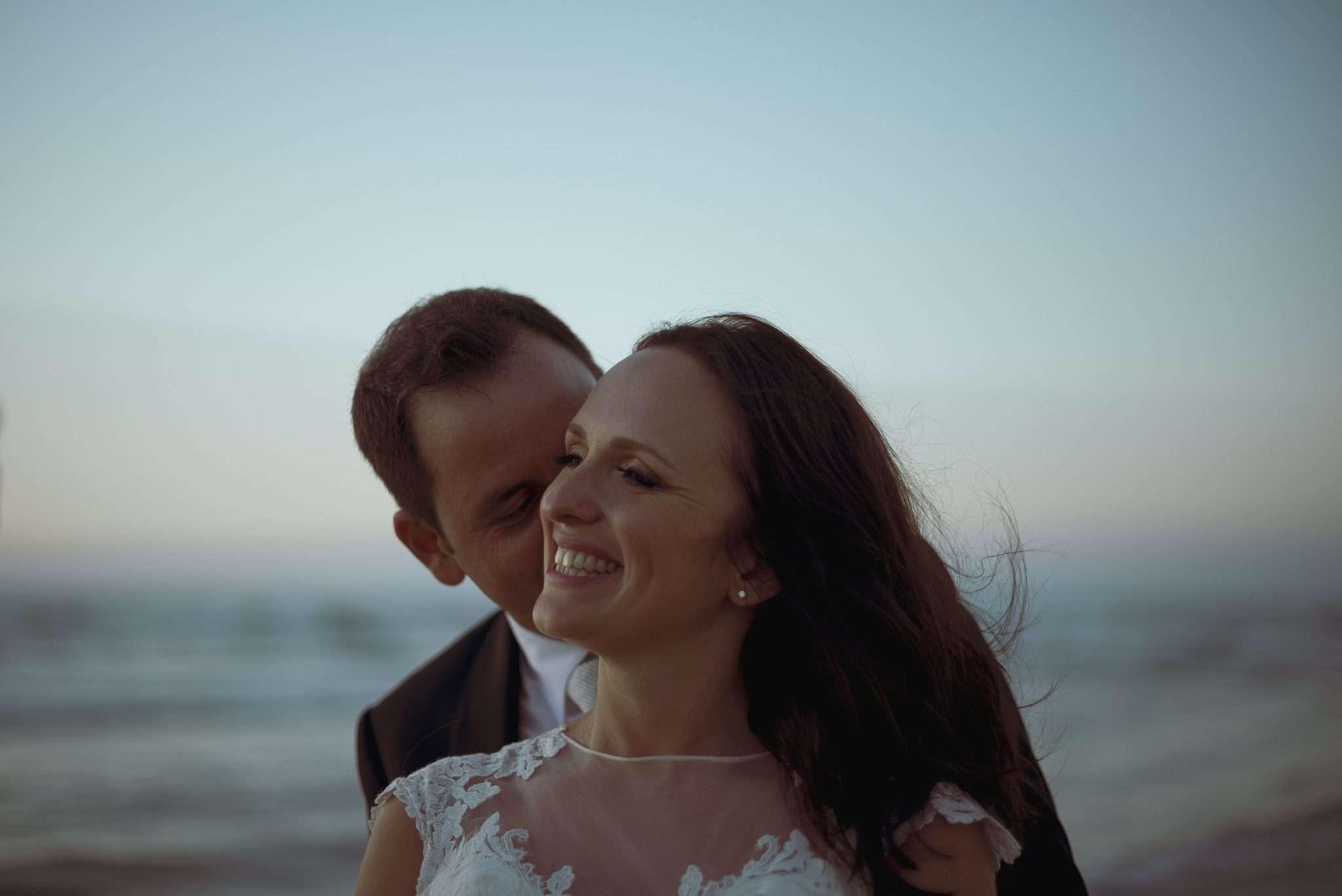 Sposo che sussurra all'orecchio della sposa che sorride