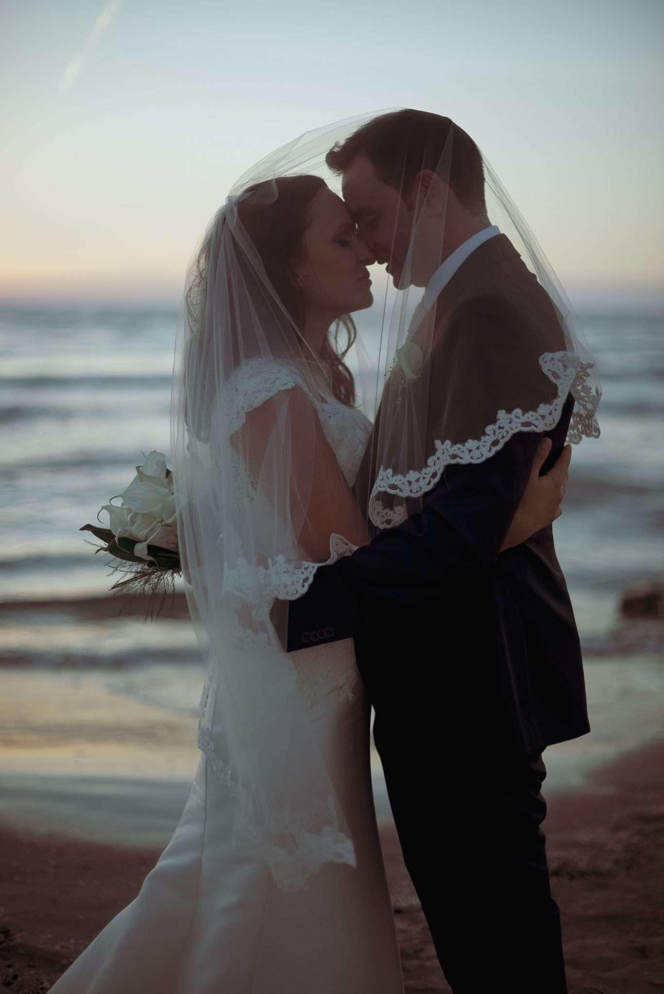 Fotografia di giovani sposi innamorati al tramonto a bacoli