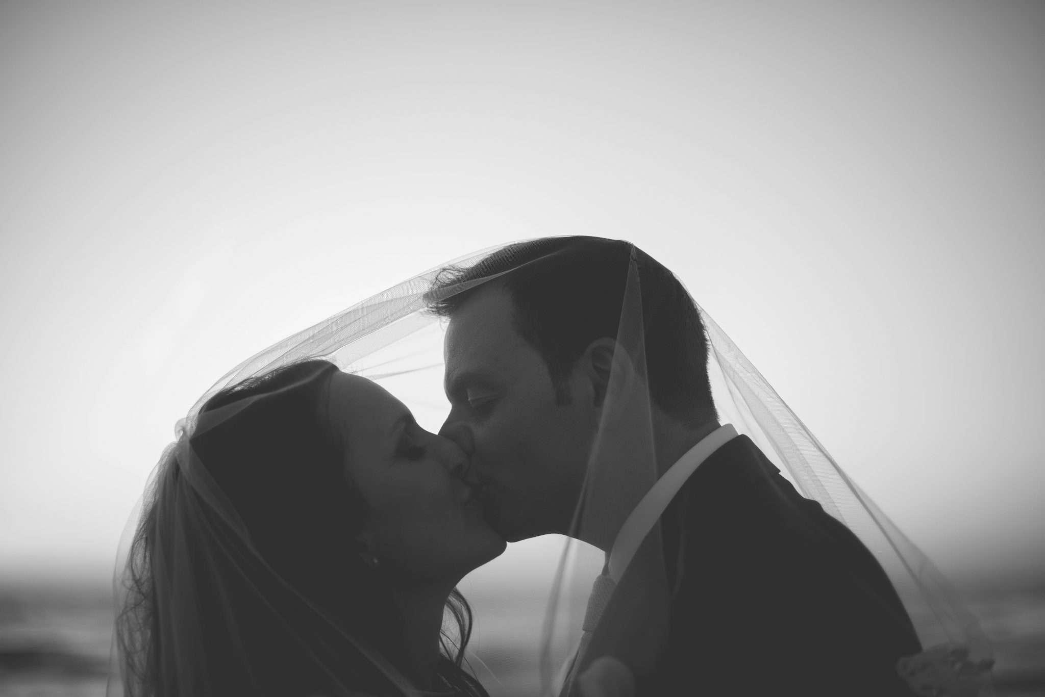 Sposi che si baciano sotto al velo