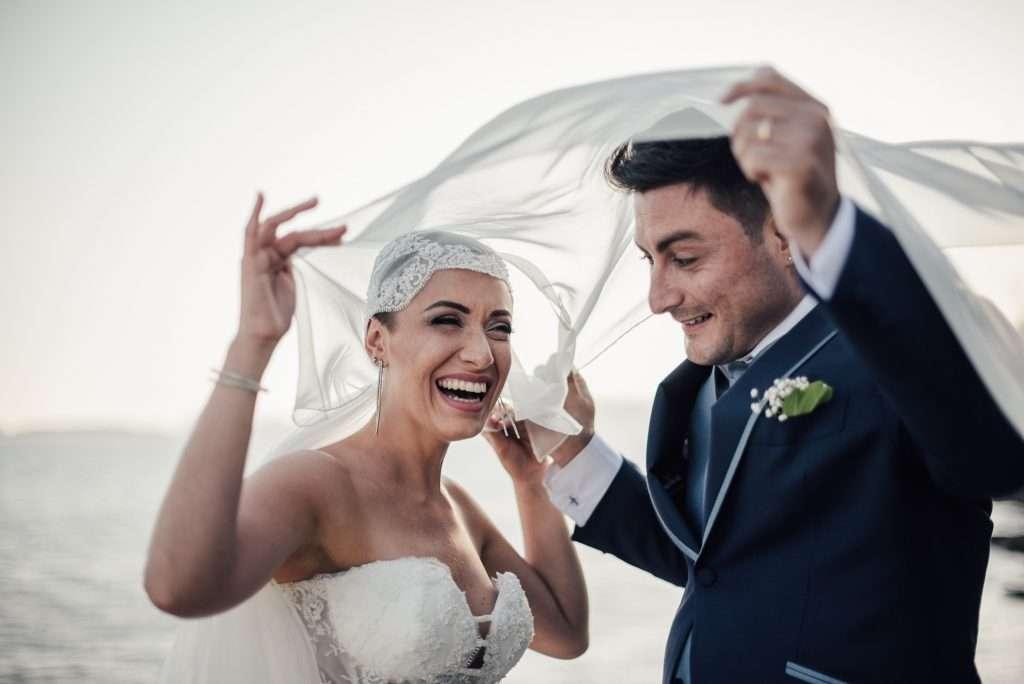 Giovani sposi che scherzano e si divertono con il velo