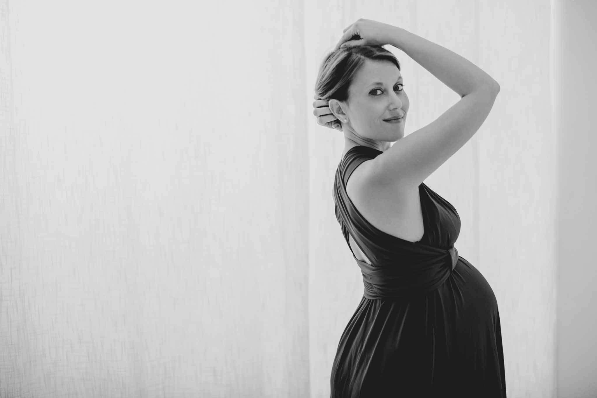 Donna in gravidanza felice mentre si tocca i capelli - Fotografia Gravidanza, Maternità e Premaman Napoli in studio e Reportage - Fotografo specializzato in genitorialità, nascita e newborn.