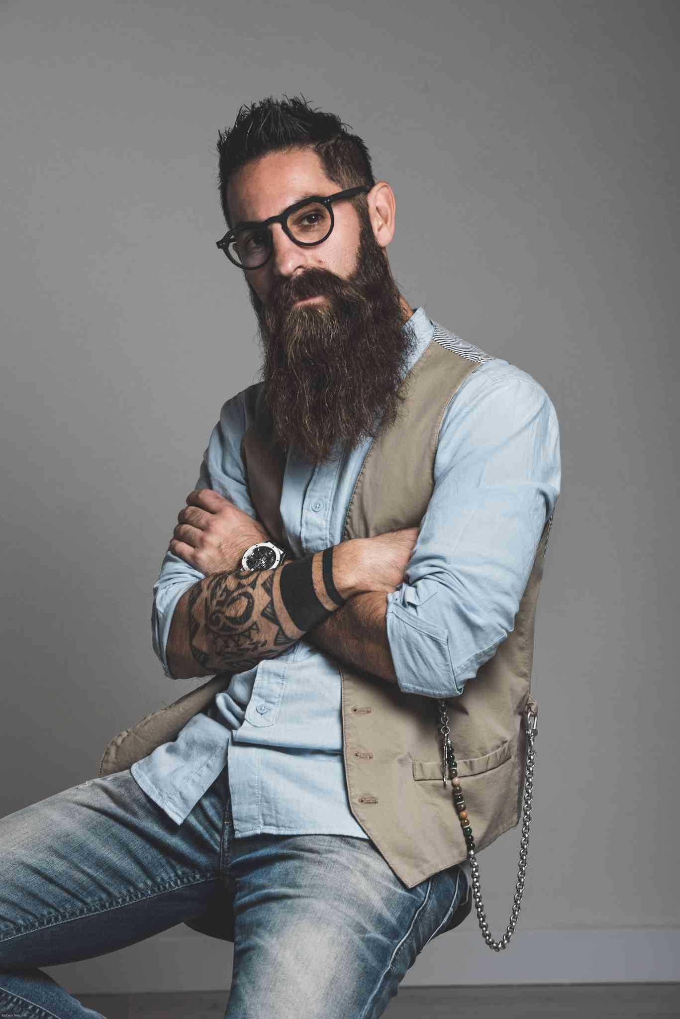 Ragazzo barba hipster seduto con braccia incrociate