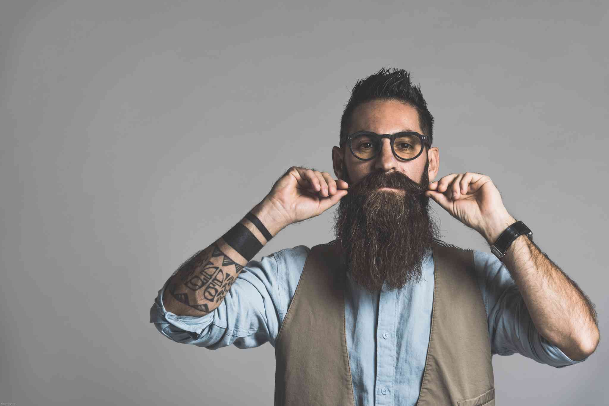 Ragazzo con barba hipster che si liscia i baffi