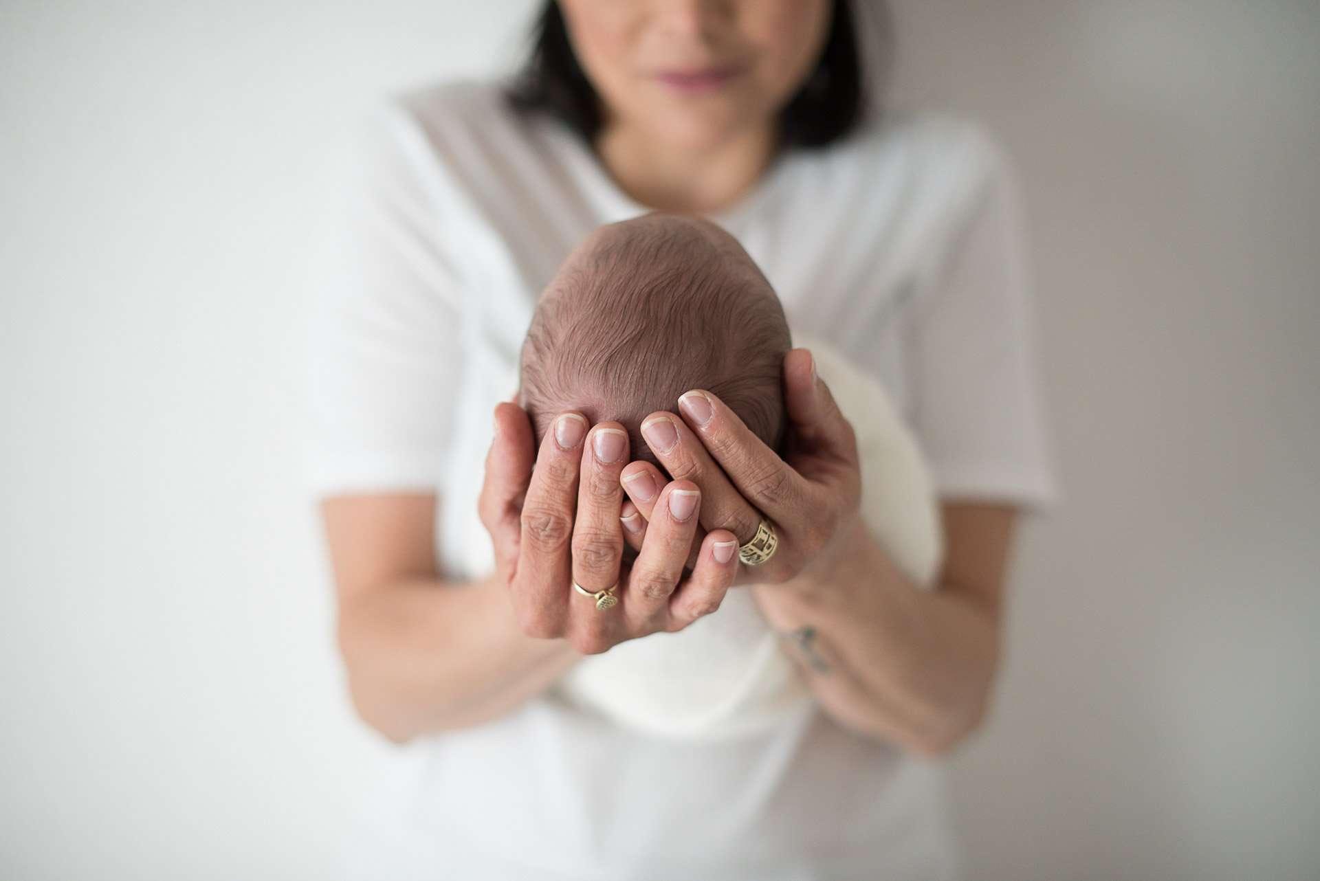 Fotografia testa bambino tra le mani della mamma