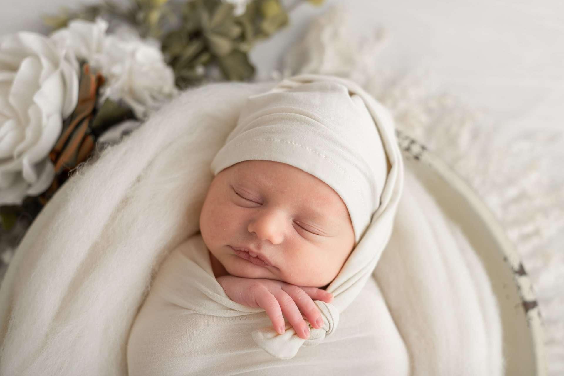 Fotografia neonato con cappellino in cesta