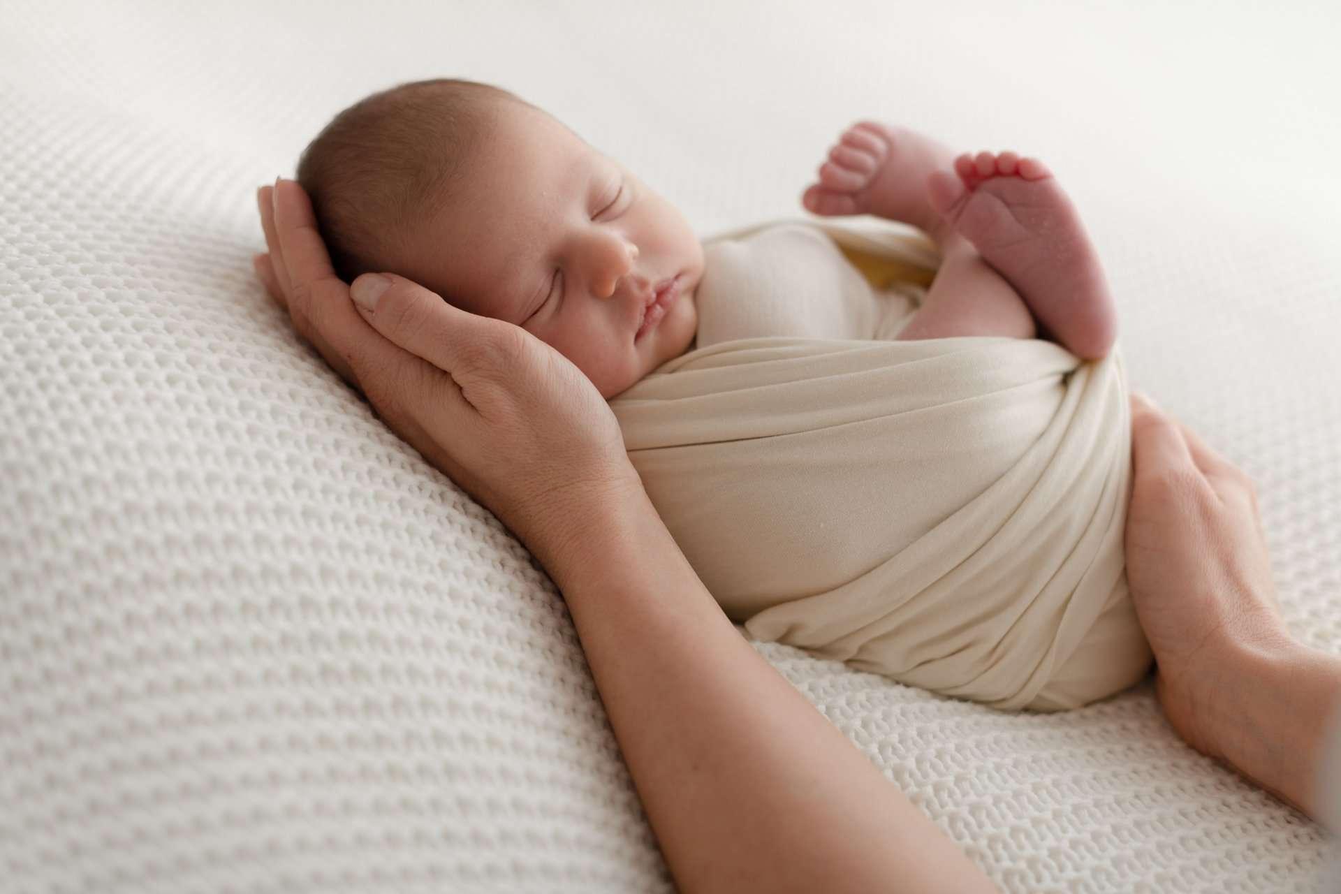 Fotografia neonato su coperta crema