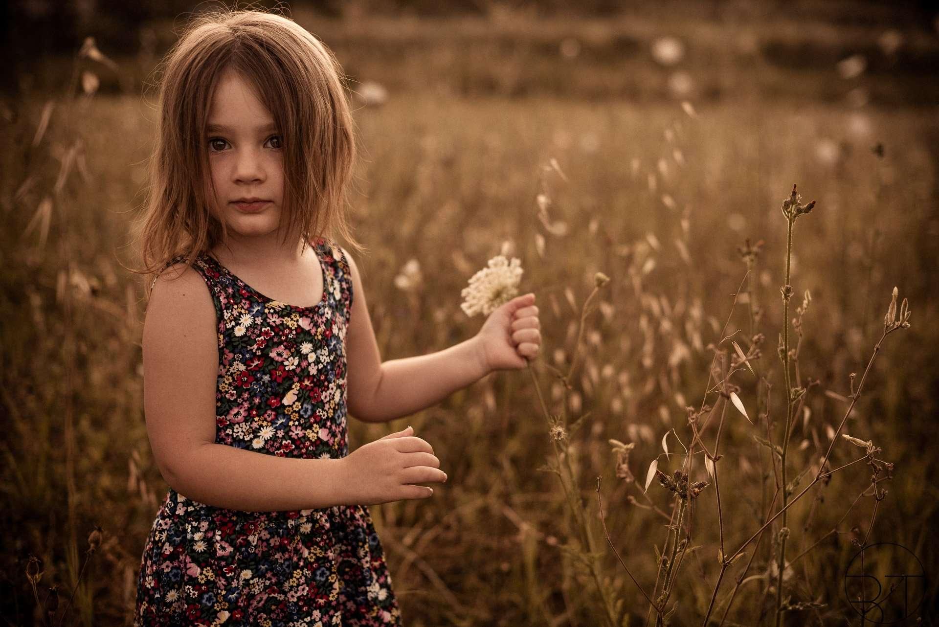 Fotografia di bambina che raccoglie fiori realizzata da Barbara Trincone Fotografo specializzato ritratti di famiglia a Napoli, Salerno, Avellino, Caserta